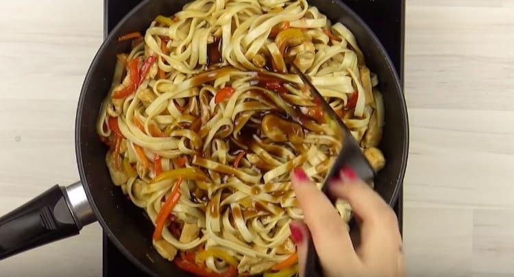 Выкладываем к овощам с курицей лапшу, добавляем оставшийся соус.