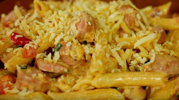 При подаче макароны с сосисками можно посыпать тертым сыром.