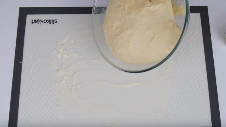 Перекладываем подошедшее тесто на присыпанную мукой поверхность.