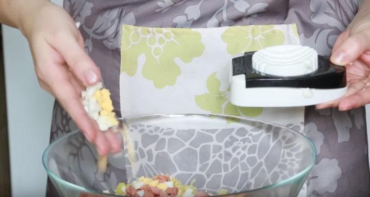 При помощи яйцерезки режем яйца.