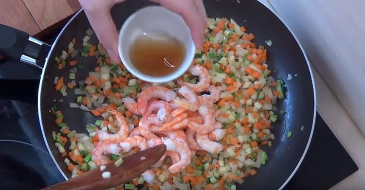 Выкладываем к овощам креветки и добавляем рисовое вино.