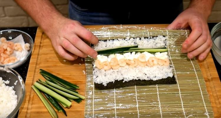 С одной стороны от сыра выкладываем креветки, а с другой добавляем огурцы.