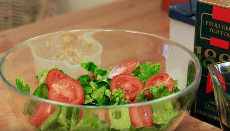 Добавляем к шпинату разрезанные пополам помидорки черри.