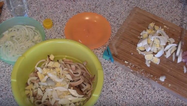 Нарезаем соломкой отварные яйца и добавляем к кальмарам.