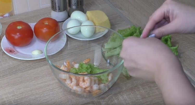 рвем на кусочки листья салата и добавляем к миску с креветками.