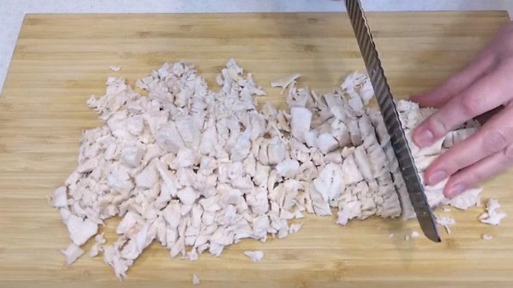 Нарезаем кусочками отварное куриное филе.