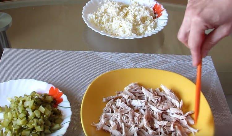 Первым слоем салата выкладываем курицу.