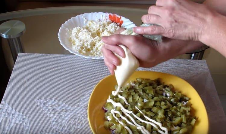 Выкладываем слой соленых огурцов и тоже покрываем их майонезом.