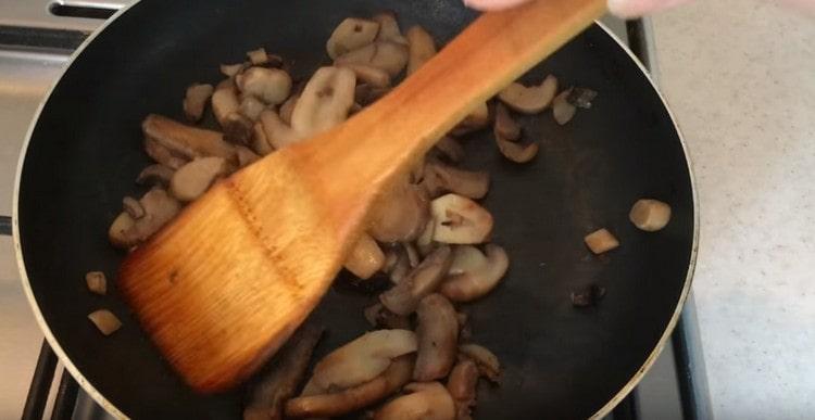 Сливаем образовавшуюся на сковороде жидкость и жарим шампиньоны до мягкости.