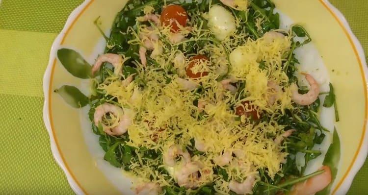 Готовый салат с рукколой, креветками и помидорами черри посыпаем тертым сыром.
