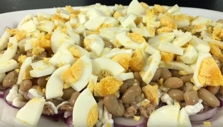 Нарезаем отварные яйца и выкладываем их следующим слоем салата.