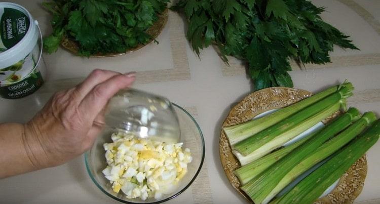 Добавляем в салат также нарезанные яйца.