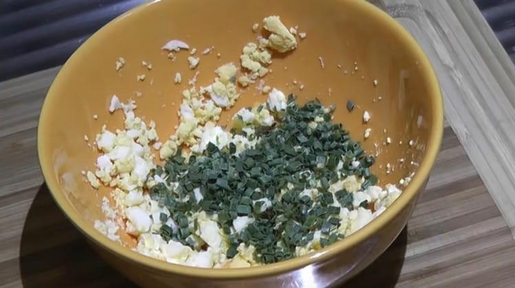 Вареные яйца крошим, перемешиваем с измельченным зеленым луком.