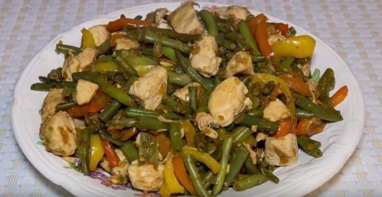 Теплый салат из стручковой фасоли с курицей готов к подаче на стол.