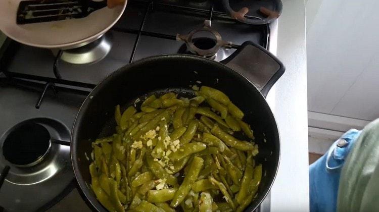 К фасоли на сковороде добавляем измельченный чеснок.