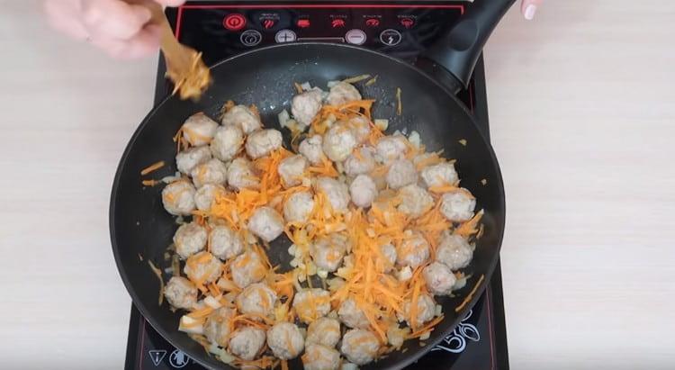 Добавляем на сковороду к фрикаделькам измельченные морковь и лук.