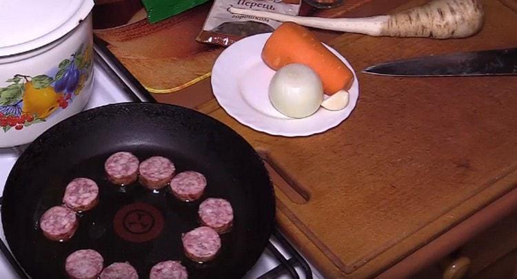 Нарезаем копченую колбасу и обжариваем на сковороде.