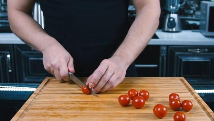 Пополам разрезаем помидоры черри.