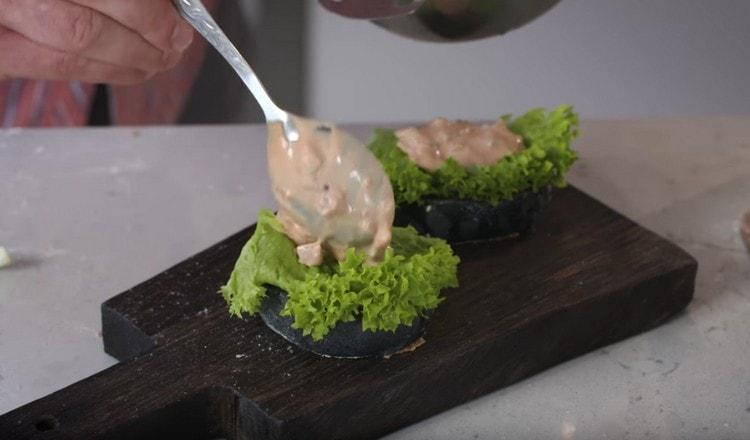 На булочку выкладываем ложку соуса, лист салата, а потом снова ложку соуса.