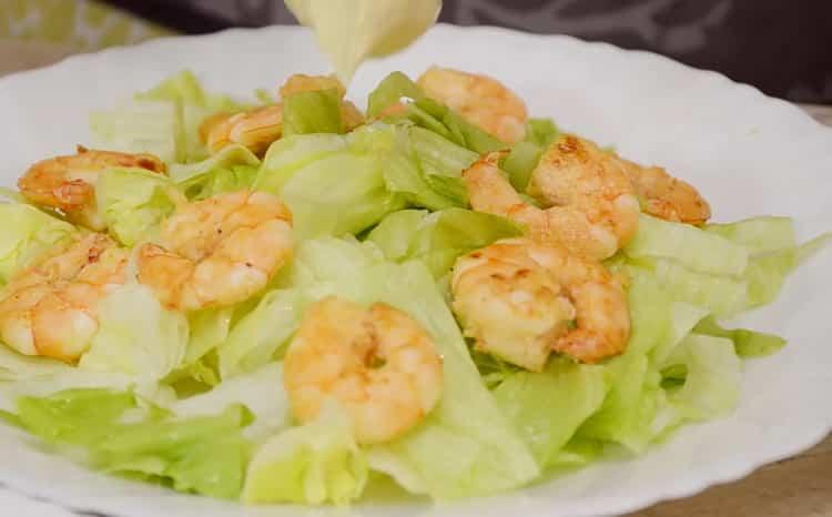 Для приготовления салата выложите креветки на листья салата
