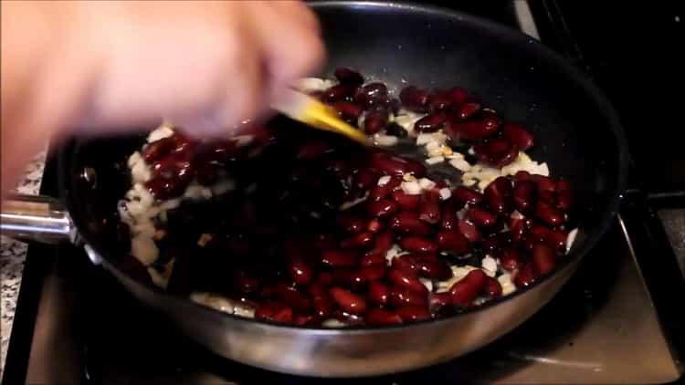 Для приготовления блюда высыпьте фасоль на сковороду