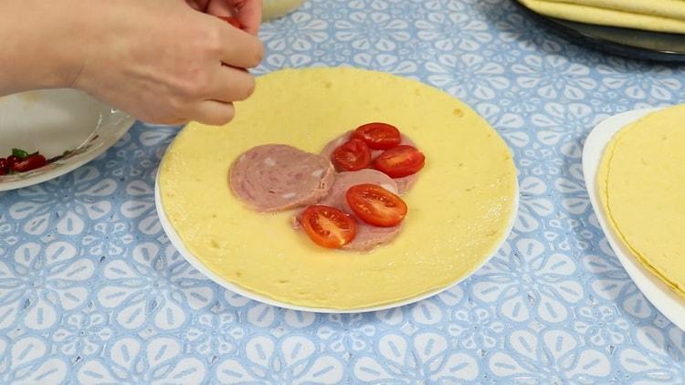 Для приготовления классической тортильи выложите колбасу на лепешку