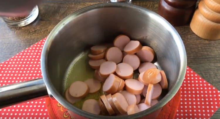Нарезаем кружочками сосиски и выкладываем в сотейник.