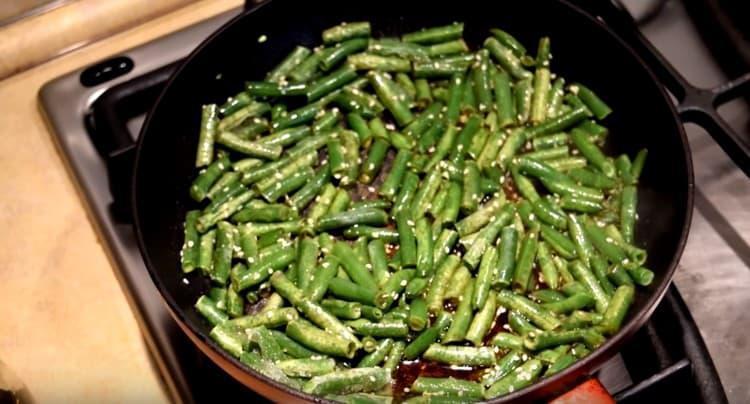 Посыпаем фасоль семенами кунжута.