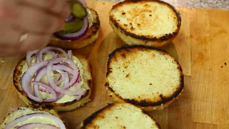Для приготовления гамбургера выложите лук на булочку