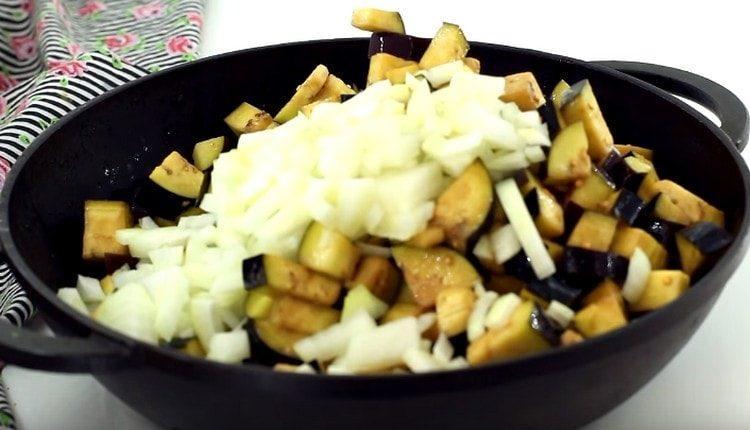 Баклажаны с луком выкладываем на сковороду и обжариваем.