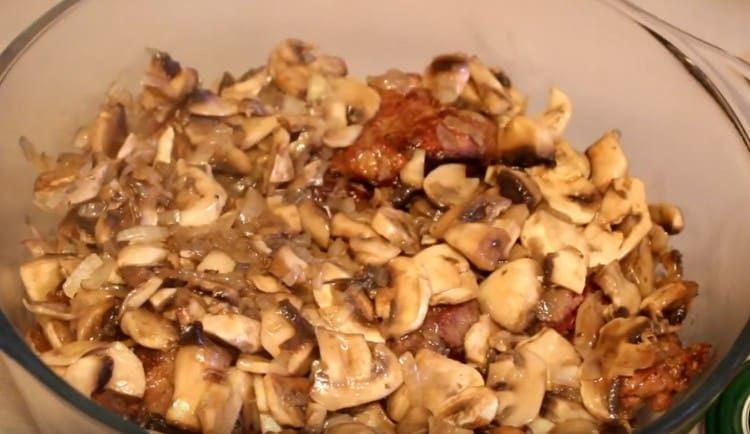 Поверх печени выкладываем грибы с луком.