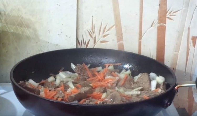 Добавляем овощи к печенке на сковороде.
