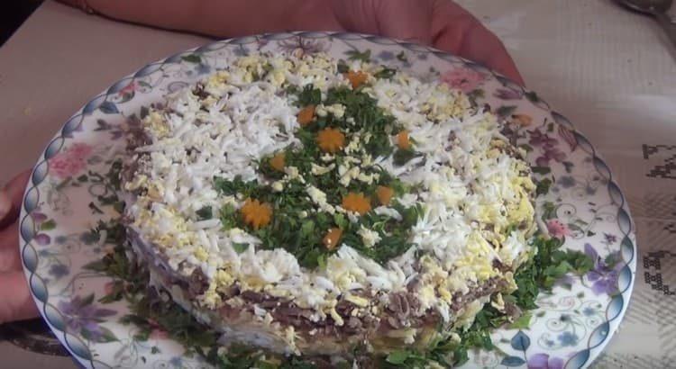 Украшаем салат из свиной печени тертым яйцом и зеленью.