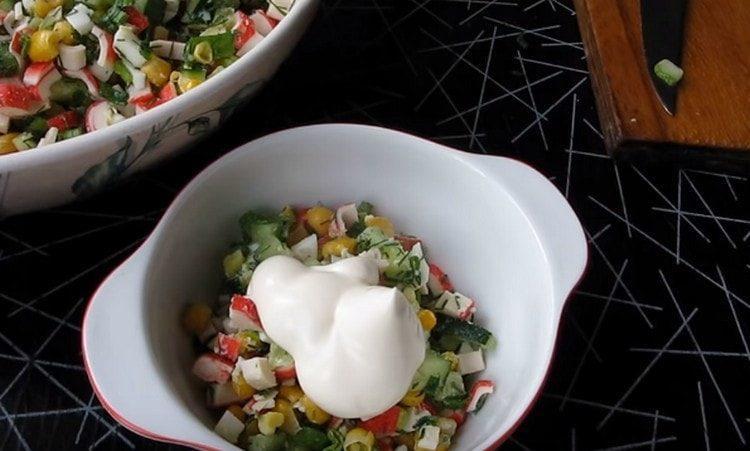Заправляем салат из крабовых палочек, кукурузы, яйца и огурца майонезом.