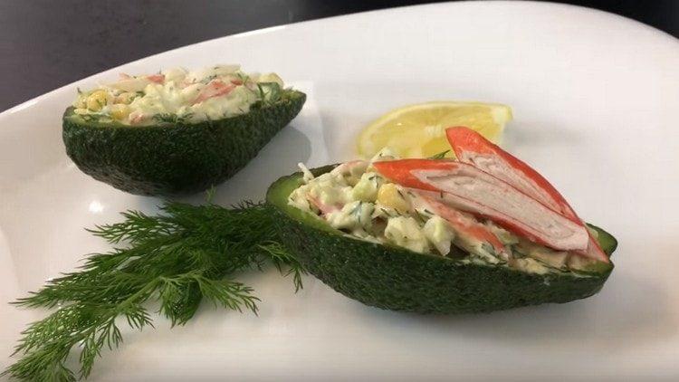 Подаем салат с авокадо и крабовыми палочками в лодочках из кожуры авокадо.
