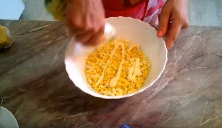 Формируем из яиц первый слой салата и смазываем его майонезом.