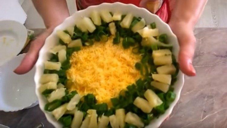 Украшаем салат с крабовыми палочками и ананасом свежей зеленью.