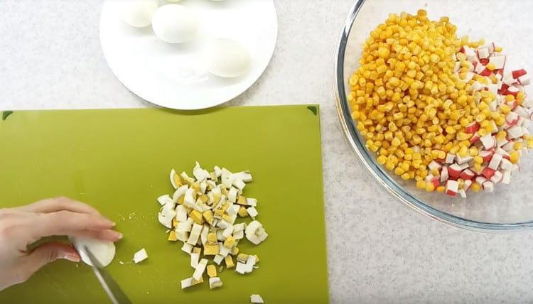Нарезаем мелко отварные яйца и добавляем в салат.