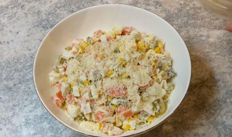 Готовый салат с крабовых палочек и огурцов посыпаем тертым сыром.