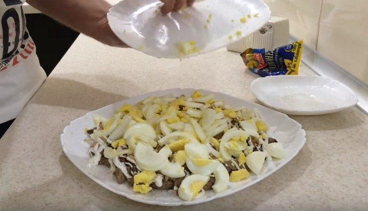 Поверх лука выкладываем яйца и смазываем майонезом.