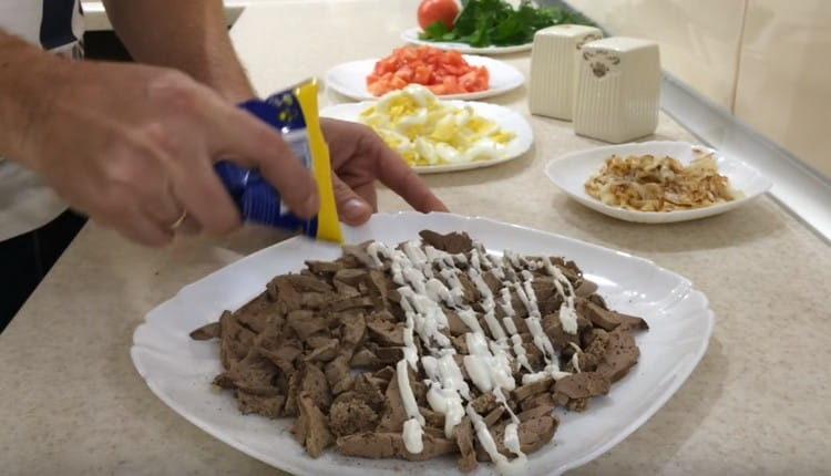 Первым слоем салата выкладываем печень, слегка смазываем ее майонезом.