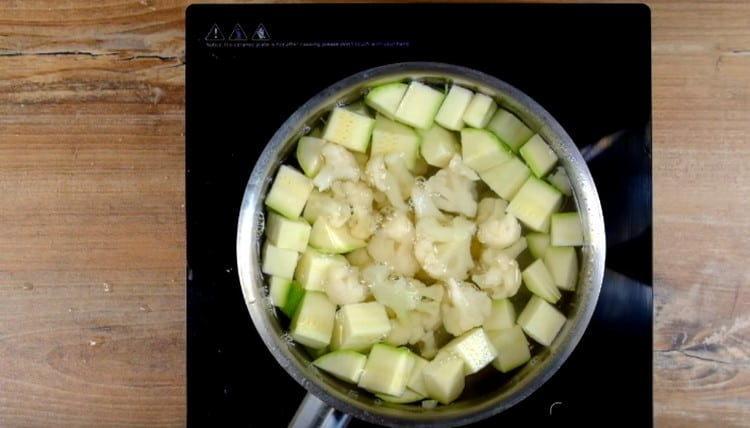 В кипящую воду выкладываем нарезанный кусочками кабачок и соцветия цветной капусты.