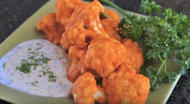 Аппетитная цветная капуста в кляре подается с соусами.
