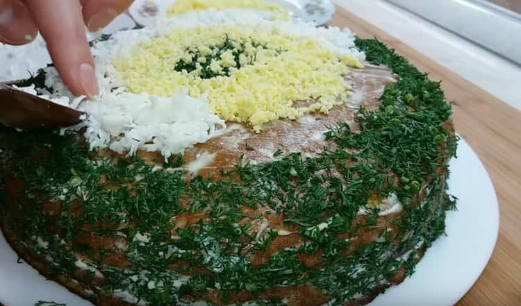 Украшаем торт измельченным укропом и тертым яйцом.