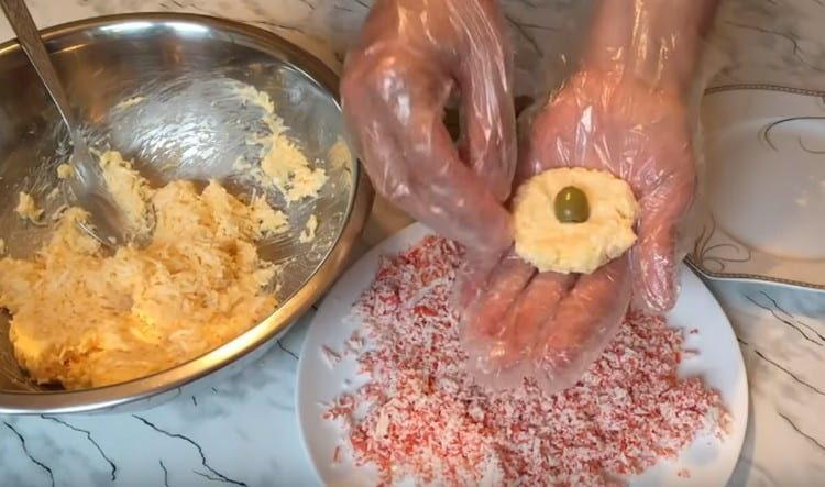 Из сырно-яичной массы формируем лепешку и кладем на центр оливку.
