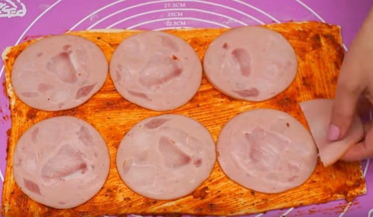 На тесто раскладываем нарезанную кружочками вареную колбасу.