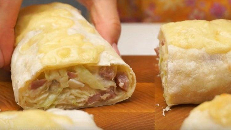 рулет из лаваша посыпаем сыром и запекаем в духовке, а затем нарезаем на порции.